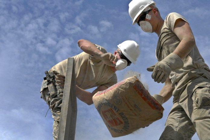 stavbári s maskami na tvári cement