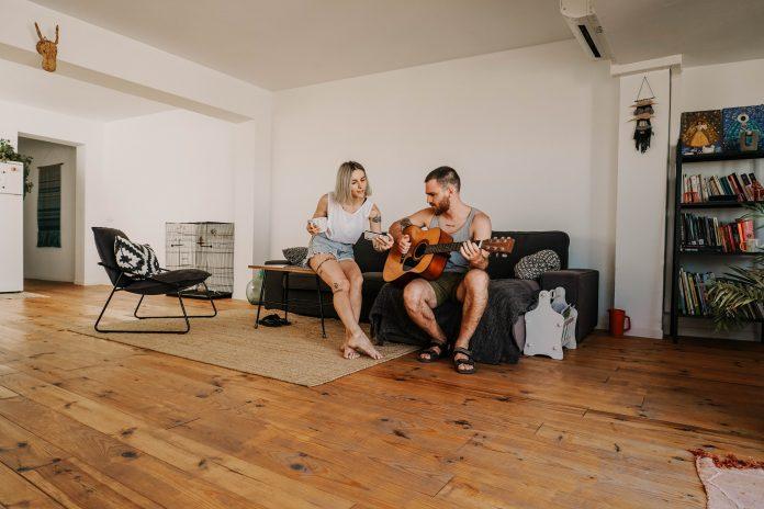 mladý pár gitara obývačka