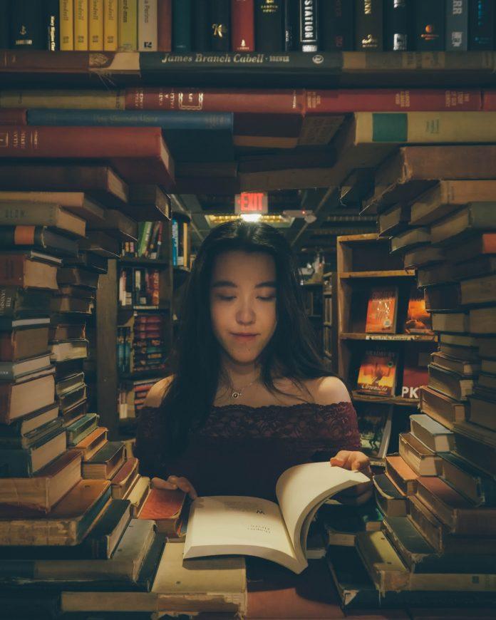 mladá žena čítajúca knihy v knižnici