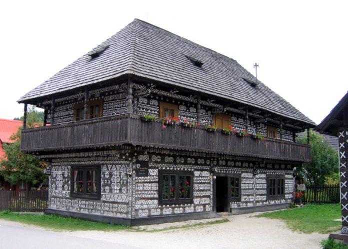 zdobený drevený dom s bielou výzdobou ľudovej architektúry zo Slovenska