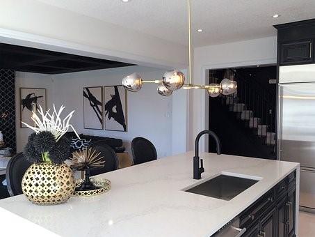 interiér bielej farby doladený čiernymi doplnkami a zlatým svietidlom
