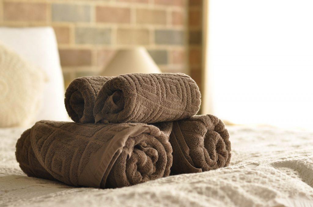 mäkučké a jemné uteráky na položené na posteli v hotelovej izbe
