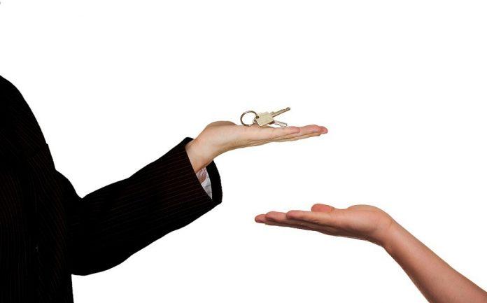 muž podávajjúci žene kľúč od jej novej nehnuteľnosti