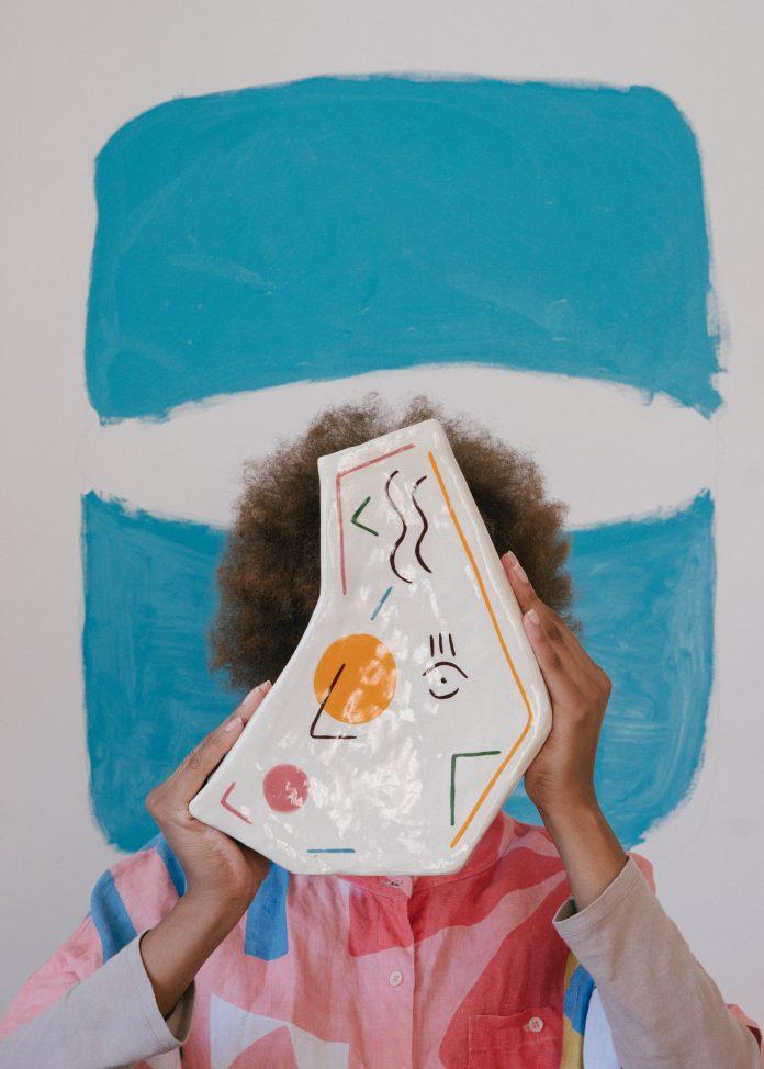 brčkavá žena drží v ruke asymetrickú dlaždicu