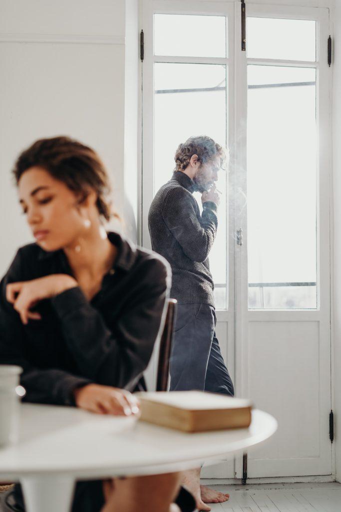 muž v čiernom roláku fajčiai cigaretu a mladá smutná žena sediaca za stolom