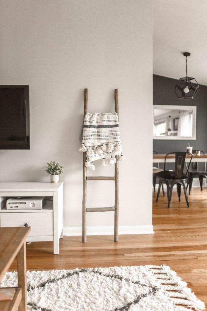 Moderná obývačka v škandinávskom štýle s dreveným rebríkom a dekou