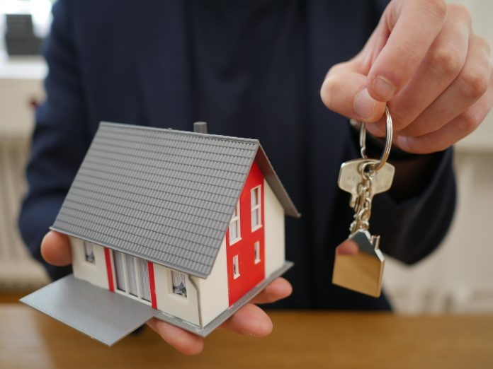 muž držiaci maketu domu a kľúč od domu