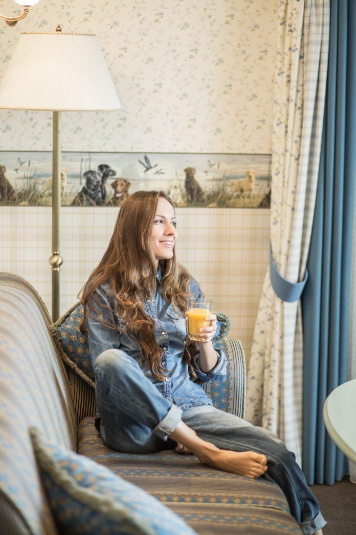 mladá žena drží v rukách pomarančovú štavu a pozerá do ďiaľky