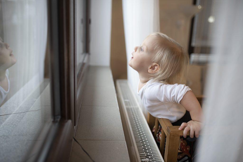 dieťatko sledujúce prírodu z okna