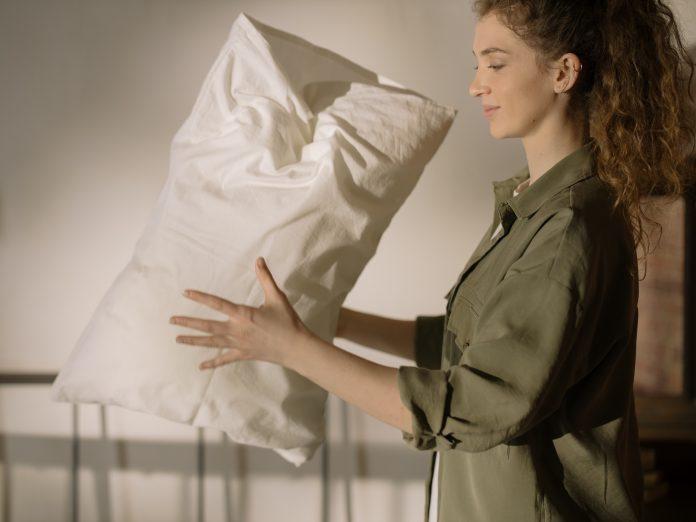 mladá žena práši biely vankúš v spálni