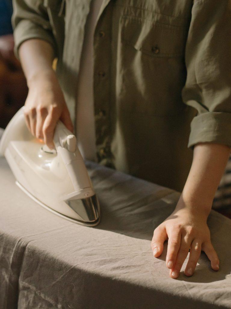mladá žena žehlí posteľnú bielizeň tmavej farby