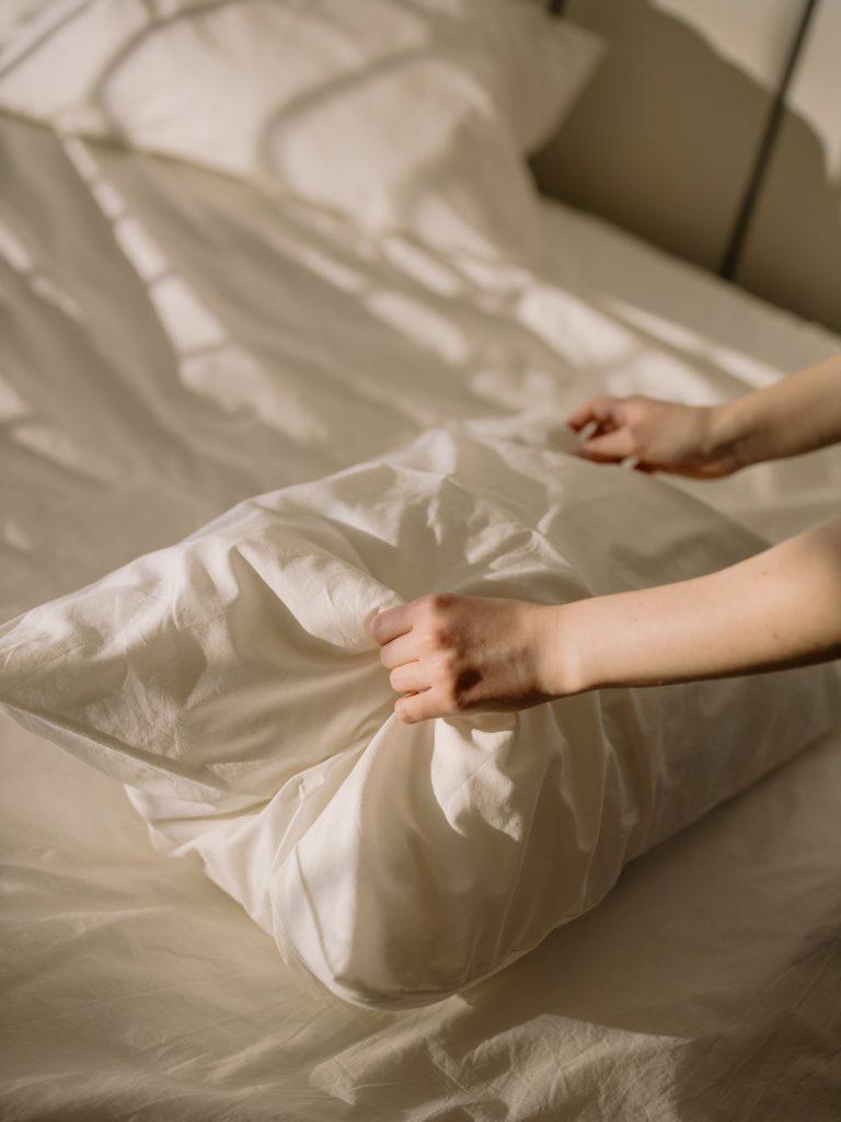 ženské ruky prášia biely vankúš na posteli