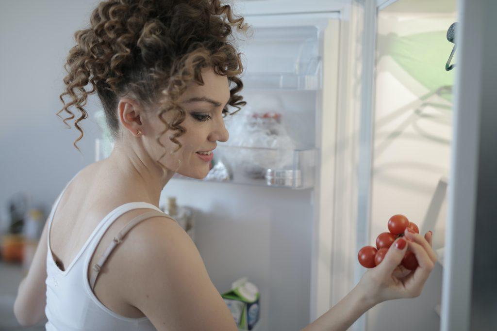 mladá žena pred chladničkou drží ruke čerstvé paradajky