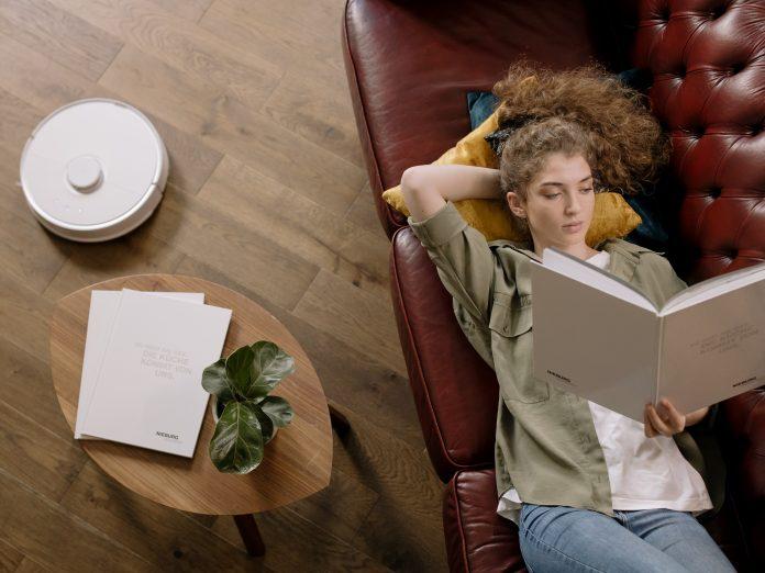 oddychujúca žena s knihou na gauči, robotický vysávač v akcii