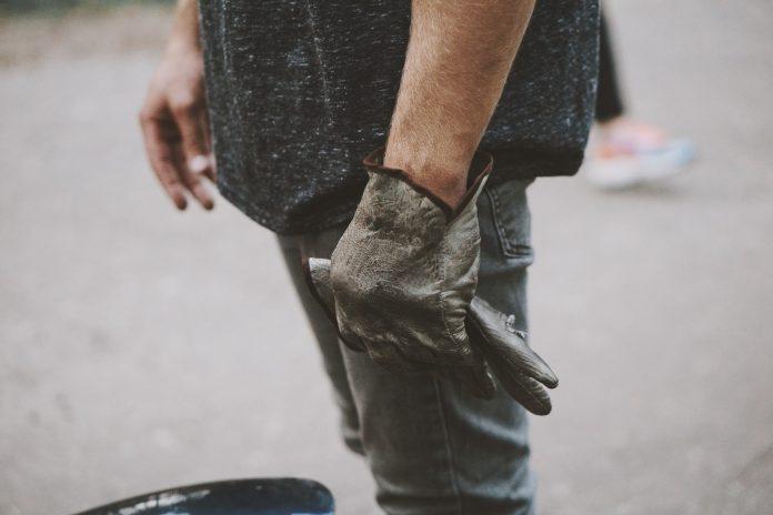 mužské ruky s čiernymi rukavicami na prácu v teréne