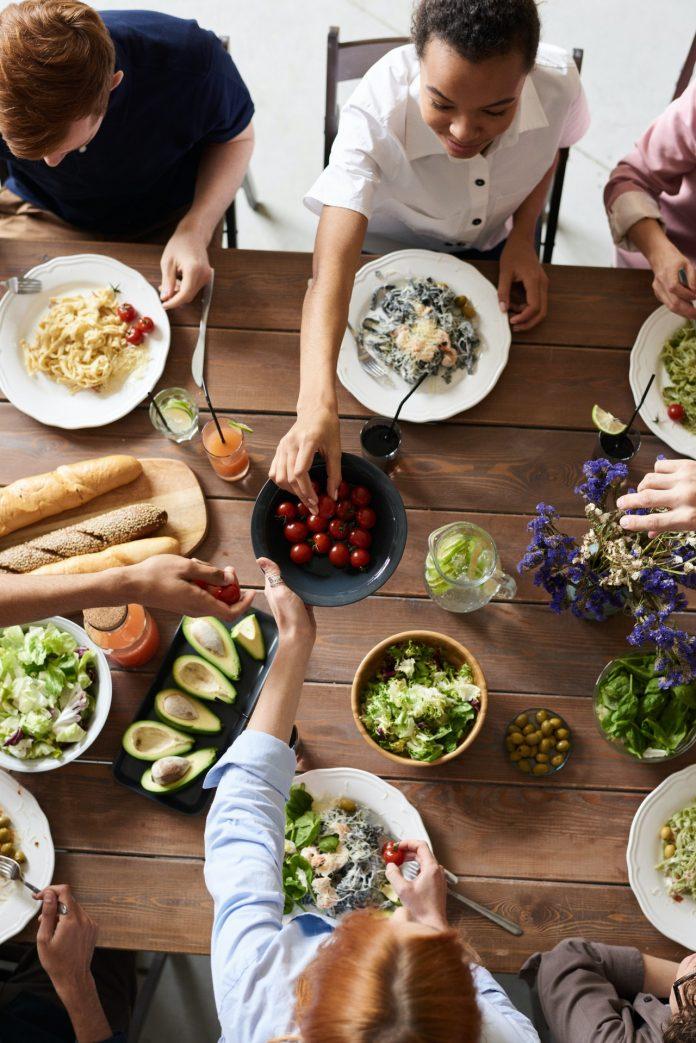 veselá partia mladých ľudí pri kuchynskom stole