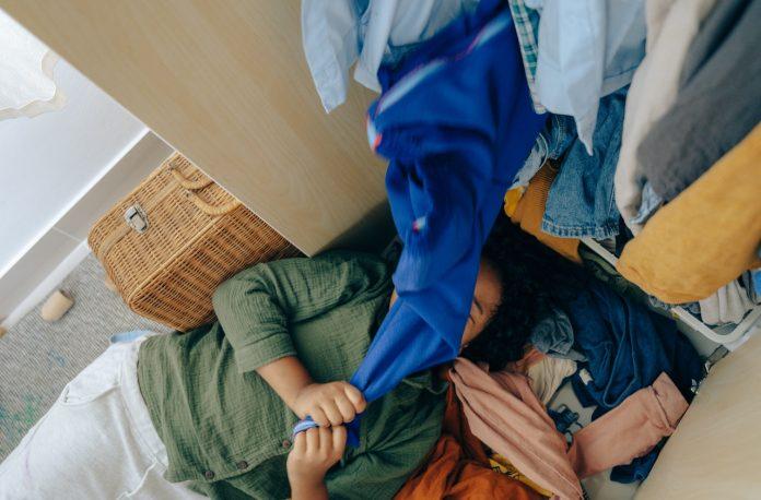 žena ležiaca pred šatníkom s neuloženou bielizňou