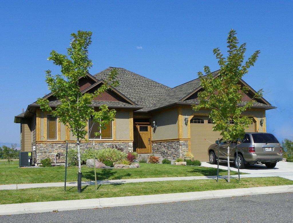 dom so záhradou a novým automobilom zaparkovaným pred garážou