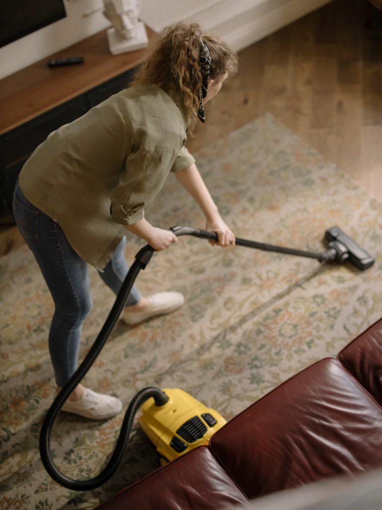 krásna mladá žena čistiaca sj domov od prachu pomocou vysávaču