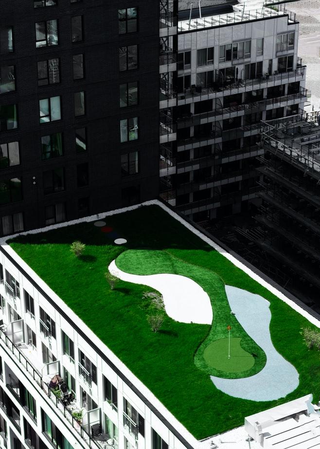 zelená strecha na modernej budove v centre mesta medzi budovami