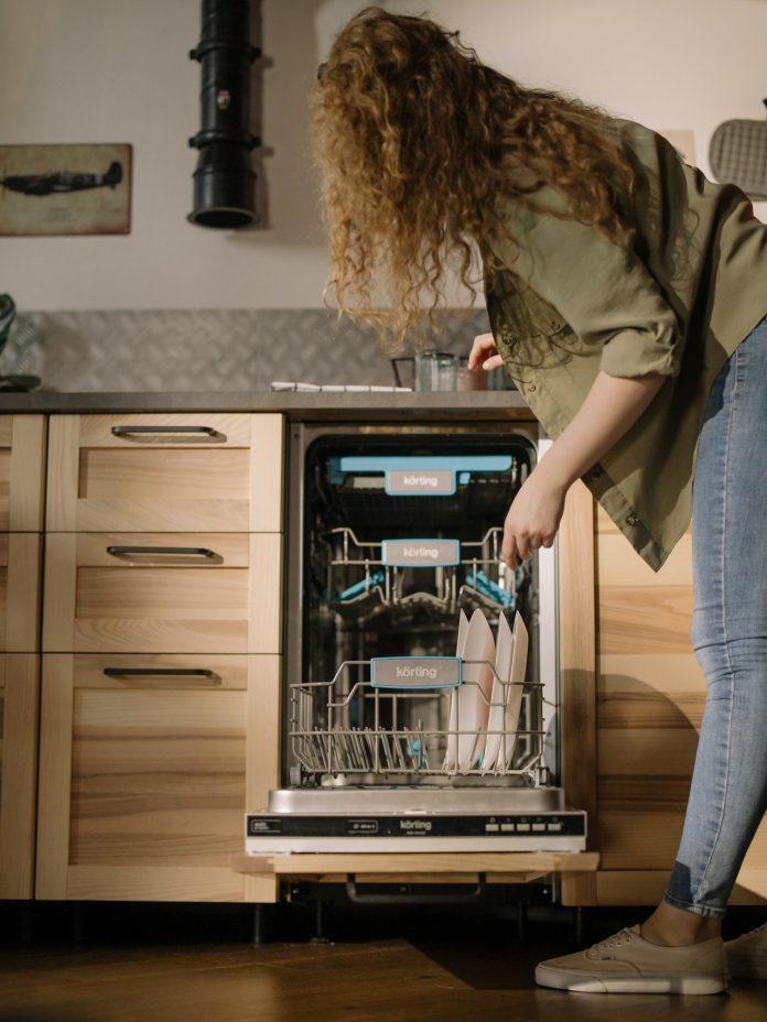 mladá žena stojaca pred čistou umývačkou riadu v smart kuchyni