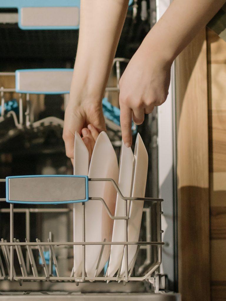 mladá žena vkladajúca špinavý riad do umývačky riadu