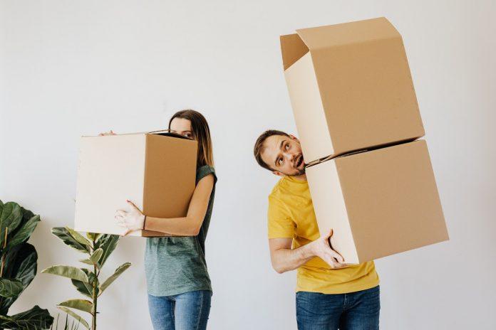 mladý pár s kartónovými krabicami v obývacej miestnosti