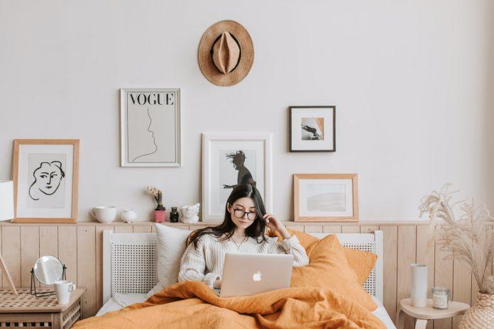 pani s laptopom na svojej posteli s oranžovými obliečkami
