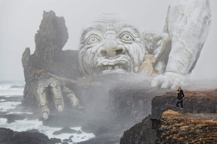 žena stojaca na útese pred obrovským trollom