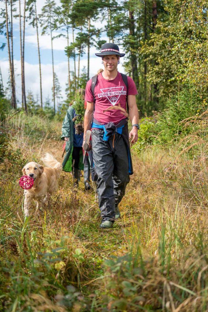 mladý muž kráčajúci lesnou cestičkou spolu so svojím psom