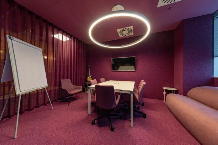 zázemie pre mladý kolektív vo firme - kancelárie v cyklaménovej farbe s kreslami a gaučom