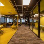 chodba moderných kancelárskych priestorov so sivým kobercom