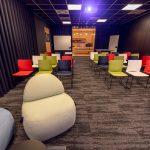 Zasadacia miestnosť s farebnými stoličkami a kreslami v modernej firme