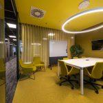 spoločenská zasadačka žltej farby so závesmi v bledých odtieňoch a výrazným osvetlením
