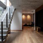 vstupná hala rodinného domu s výrazným surovým schodiskom