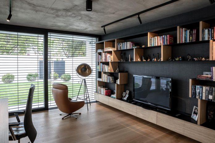 obrovské okná v obývacej miestnosti a moderné kožené kreslo vedľa knižnice