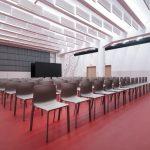 multifunkčný priestor pre návštevníkov divadelnej sály s výraznou červenou podlahou