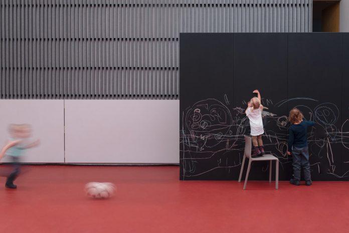 multifunkčný priestor pre návštevníkov sály s výraznou červenou podlahou a kreatívnou stenou