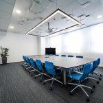 zasadacia miestnosť s krásnymi modrými kreslami a veľkým rokovacím stolom