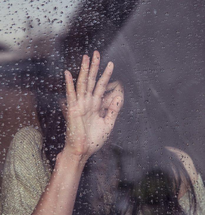 mladé dievča stojace za zaroseným oknom