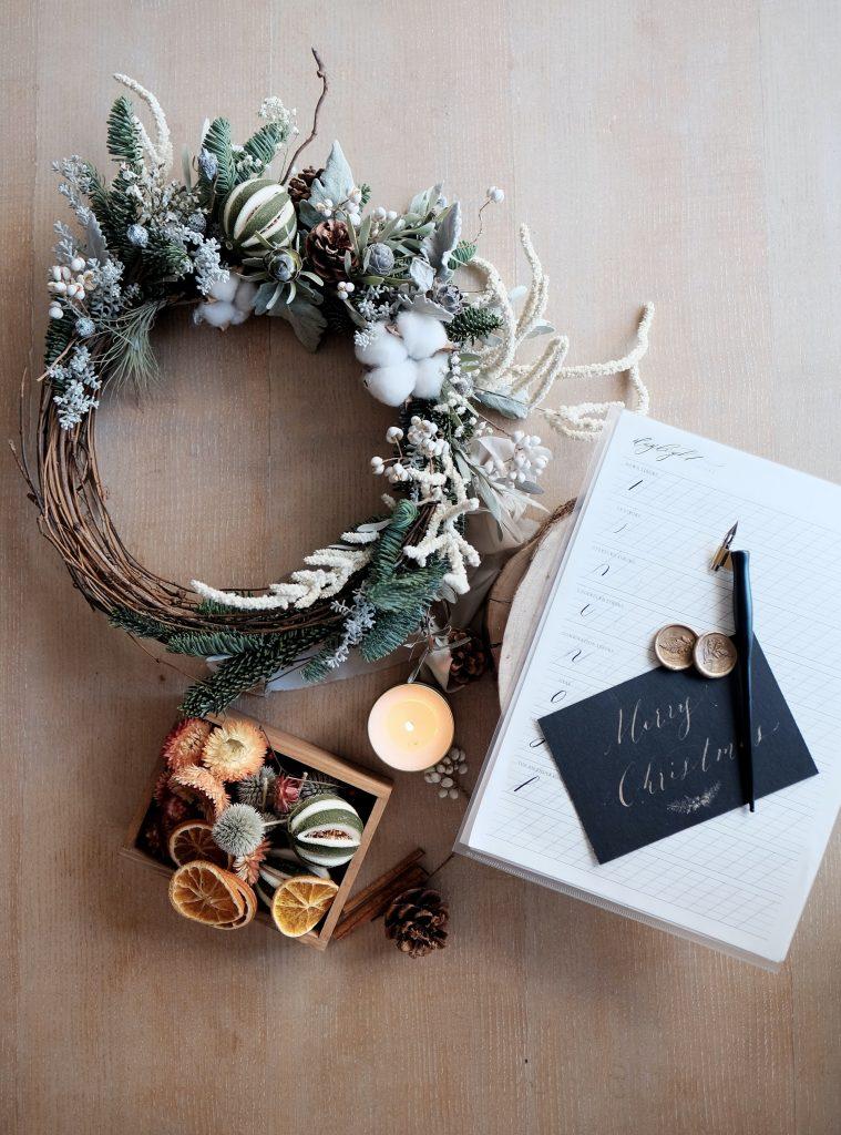 krásny vianočný veniec na stole spolu so sušeným ovocím a zápisníkom