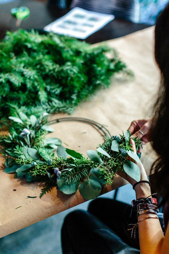 mladé dievča vytvára zo zeleného ihličia a sušenej trávy adventný veniec