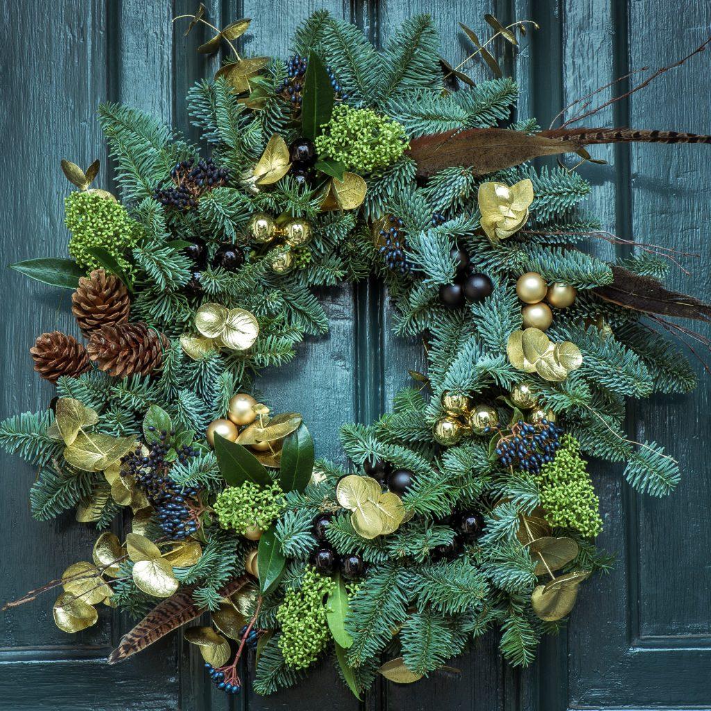 vianočný veniec s prírodnými ozdobami zavesený na vchodových dverách