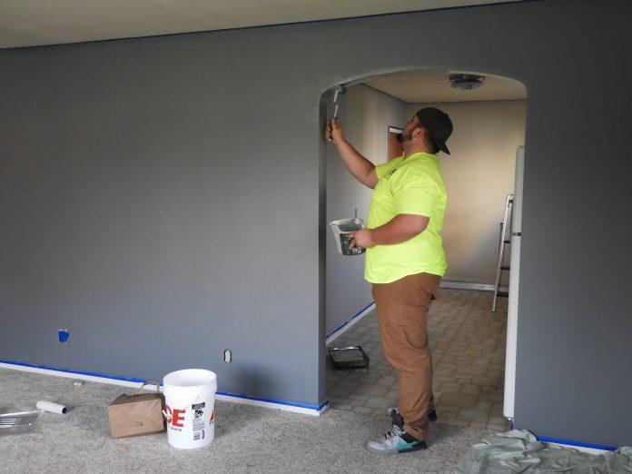mladý muž pracuje podľa manuálu a natiera miestnosť, aby opticky zväčšil priestor