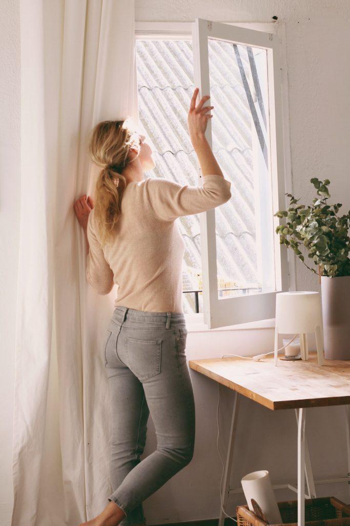 mladá žena stojaca pri okne a hľadiaca do diaľky