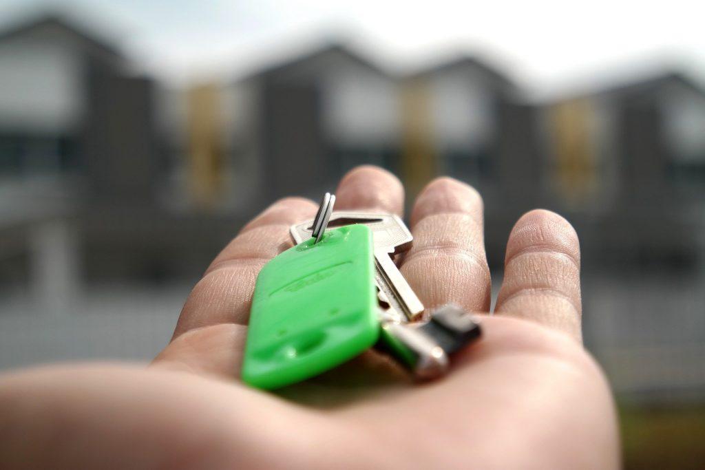 mladý muž držiaci kľúče od novej nehnuteľnosti