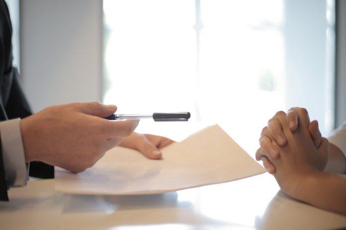 mladý muž poskytujúci potrebné dokumenty záujemcovi pre stavbu domu