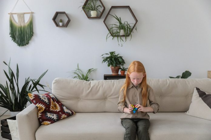 ryšavé dievčatko sediace na gauči v modernom interiéri zariadenom v roku 2020
