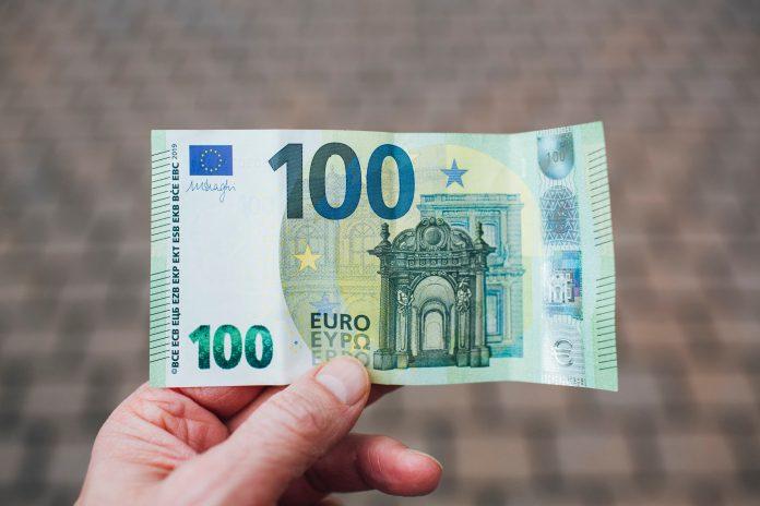 muž držiaci stoeurovú bankovku