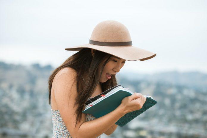 mladá žena čítajúca knihu počas krásneho letného dňa